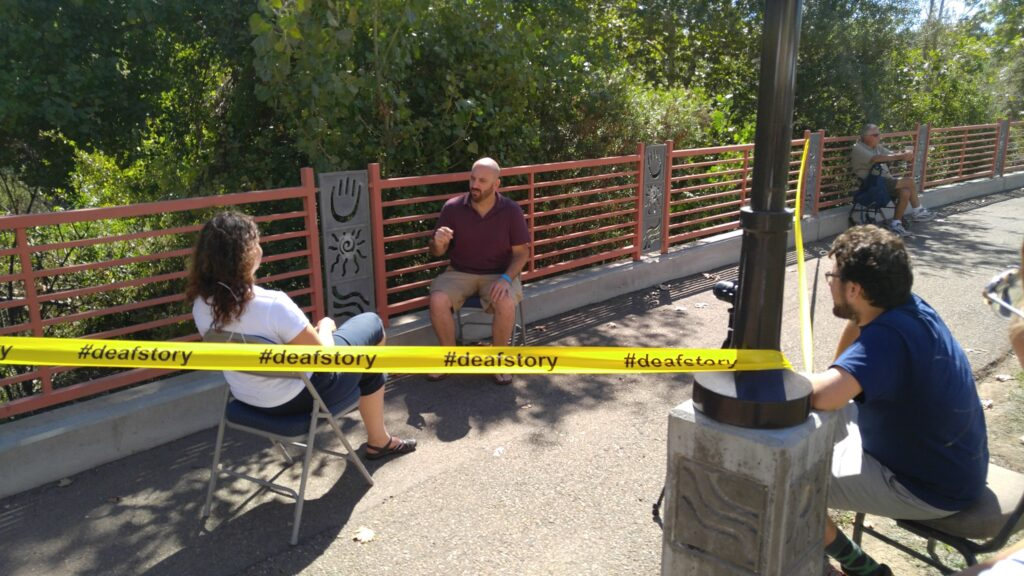 outdoor scene in san diego at the deaf festival with the words deafstory on what looks like police tape
