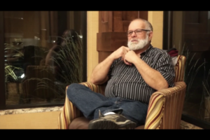 Keith Drown sits in hotel lobby telling a story in asl american sign language