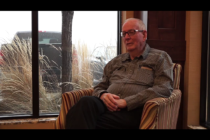 Jerry Wilding sitting in a hotel lobby chair telling a story in american sign language