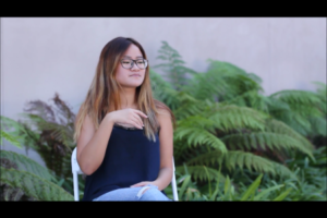 Kendra telling a story in american sign language outside with some nice ferns in the background